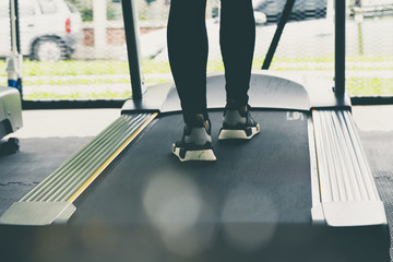 Woman legs on Treadmill or tracking machine in fitness center