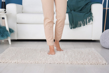 Woman walking on soft carpet at home