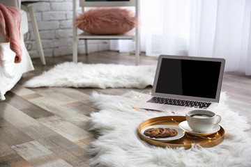 Tray with breakfast and laptop on fluffy carpet in room