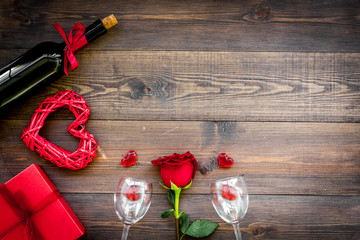 Celebrate Valentine's day. Wine, glasses, red rose, heart sign, gift box on dark wooden background top view copy space