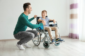 Young man taking care of little boy in wheelchair indoors