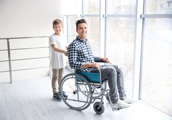 Little boy taking care of young man in wheelchair indoors