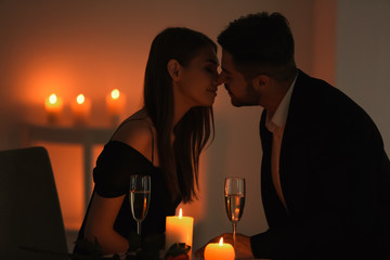 Young couple kissing while sitting at table with burning candles