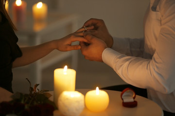 Man putting engagement ring on fiancee's finger while sitting at table with burning candles