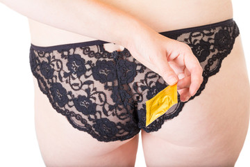 Woman holding condom behind her back on white background. Safe sex concept