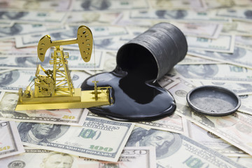 Concept of oil drilling pump, spilled oil from barrel on dollar banknote money. Business idea