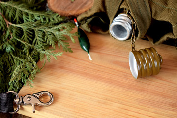 Flask, float and carabiner on a wooden board. Fishing hobby concept