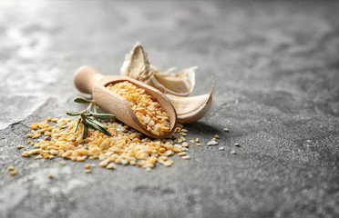 Wooden scoop with granulated dried garlic on grey background