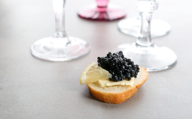 Tasty sandwich with black caviar and lemon on table