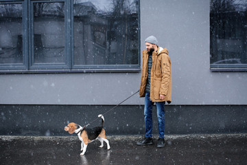Handsome young hipster walking his dog outdoors on snowy day