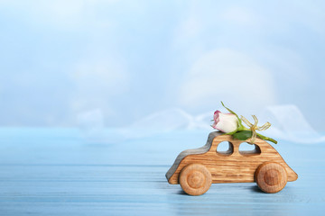 Decorative wooden car with beautiful rose on table