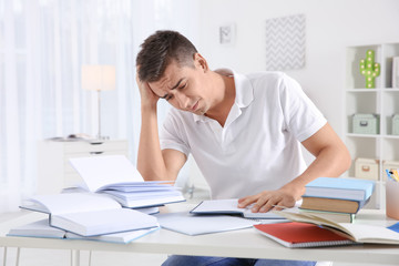 Stressed student preparing for exam at table indoors