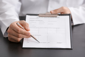 Doctor showing insurance form at table