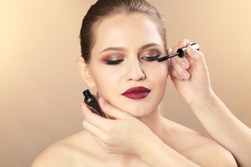 Professional visage artist applying makeup on woman's face on color background