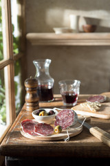 Salami and red wine served on the table