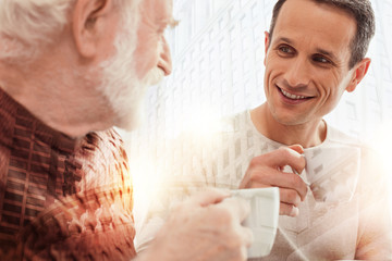 Attentive son. Young handsome smiling man sitting next to his aged father and drinking coffee with him