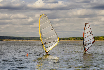 The windsurfer plays in the waves, in the vastness of the reservoir