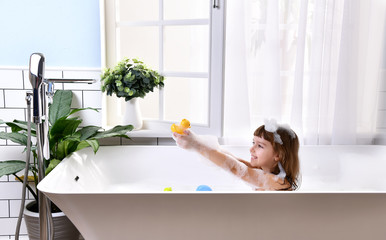 Happy little baby girl sitting in bath tub playing with duck toys  in the bathroom