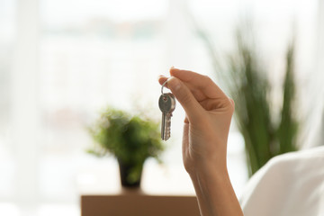 Female hand holding house key, customer buying real estate, woman buyer becoming new first time home owner, rental property purchase, mortgage investment loan, ownership concept, close up view