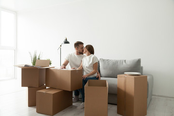 Young couple kissing sitting on sofa in living room with cardboard boxes on the floor, moving day in own home or relocation concept, happy homeowners real estate buyers starting new life together