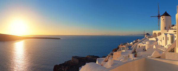 Sunset over Santorini island in Greece. Traditional church, apartments and windmills in Oia village.