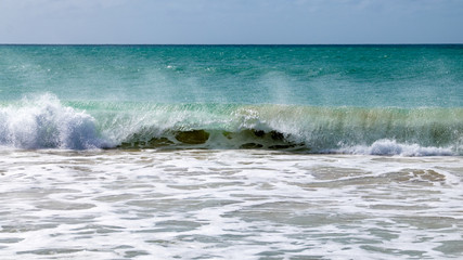 Waves breaking at the sand beach shore