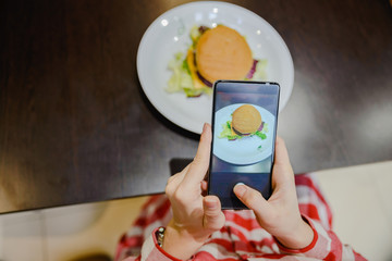 woman take picture of hamburger on her phone