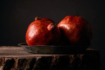 Ripe pomegranate fruit on wooden stump