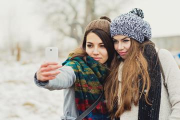 Two female teenage girl friends in winter taking a selfie on smart phone