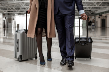 Close-up of legs of business partners are going to departure area with suitcases. They are travelling together