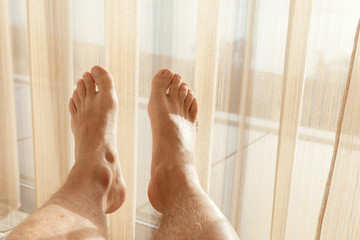 Relaxed male feet lay near wide window