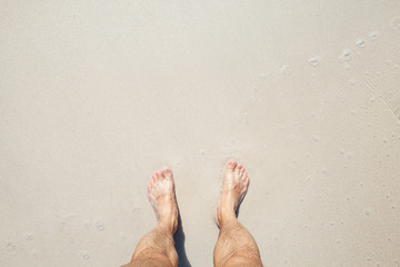 Male feet stand on white sand, top view