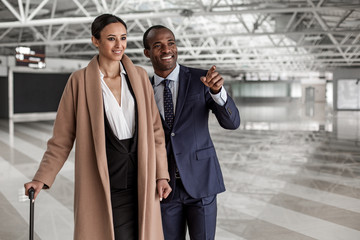 Look at that. Portrait of cheerful young man and woman are standing at terminal lounge with suitcases. Excited businessman is pointing finger forward while female is smiling. Copy space in right side