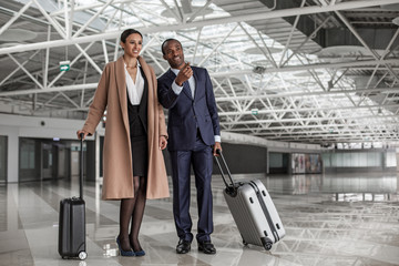 Look here. Full length portrait of delighted successful business partners are standing at airport lounge with suitcases. Man is pointing finger while woman is expressing gladness. Copy space