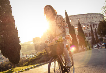 Beautiful young woman in colorful fashion long dress riding bike in front of colosseum in Rome at sunset on a road with trees. Happy attractive girl tourist with straw hat in colle oppio. Lens flare
