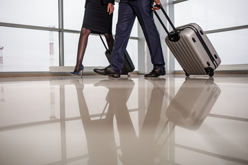 low angle close up of legs of elegant woman and businessman are going along airport lounge. They are carrying their suitcases. Copy space