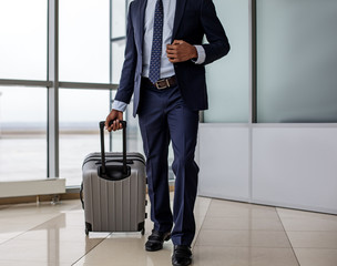 Important business trip. Elegant businessman wearing formal clothes is standing with his luggage at airport building. He is waiting for boarding
