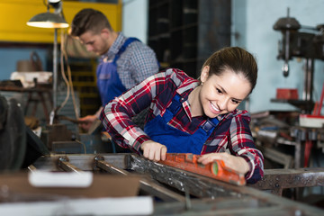 Girl master working with level in workplace