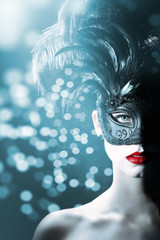 Junge hübsche Frau mit Federn Maske blickt cool