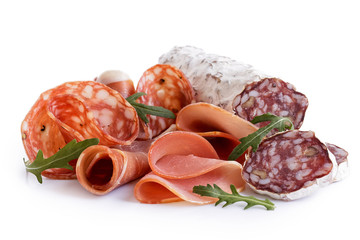 Mixed air cured sliced meats isolated on white. Rocket garnish.