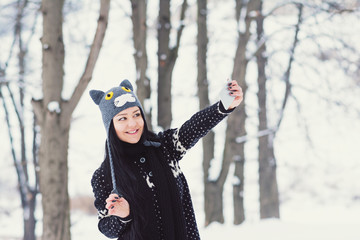 Cheerful young woman in knitted cat hat outdoors in winter in park taking a selfie on smart phone