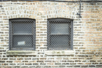 Two cage covered windows on brick wall