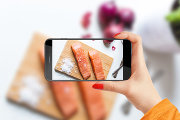 Girl taking picture of salmon slices on wooden plate with her phone