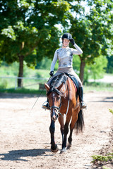 Training is finished. Girl riding a horse at equestrian school
