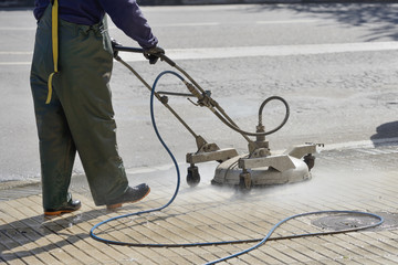worker washes the pavement