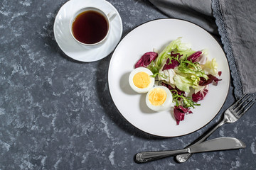 Light breakfast. Boiled eggs, salad mix and cup of coffee