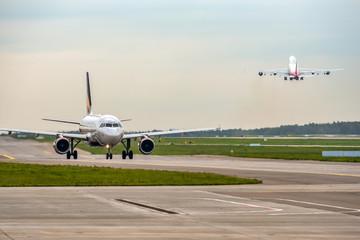 Keuken foto achterwand Vliegtuig Modern passenger airplane taxiing while big widebody aircraft taking off at airport.
