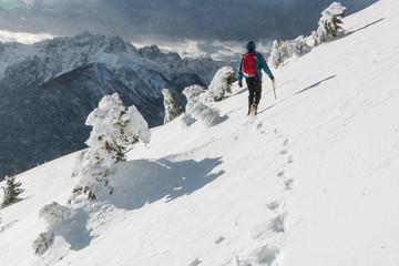 Mountaineer walking on the snowy slope of theDovska Baba mountain in Karavanke range in a wind, Slovenia