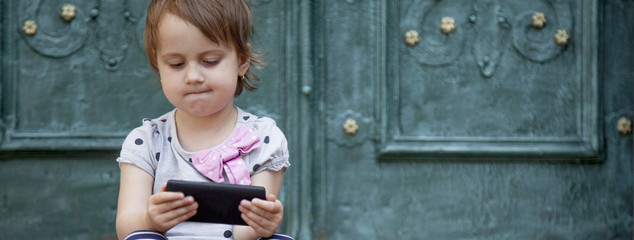 Social Media addiction. beautiful child girl  holding phone (psychological problems, media mania, education)
