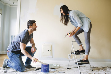 Man and woman smiling at each other while paining interior wall.